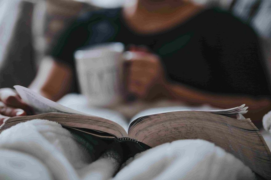 A person sitting on a bed or couch and holding a coffee mug in one hand and reading a book, turning a page with the other hand.